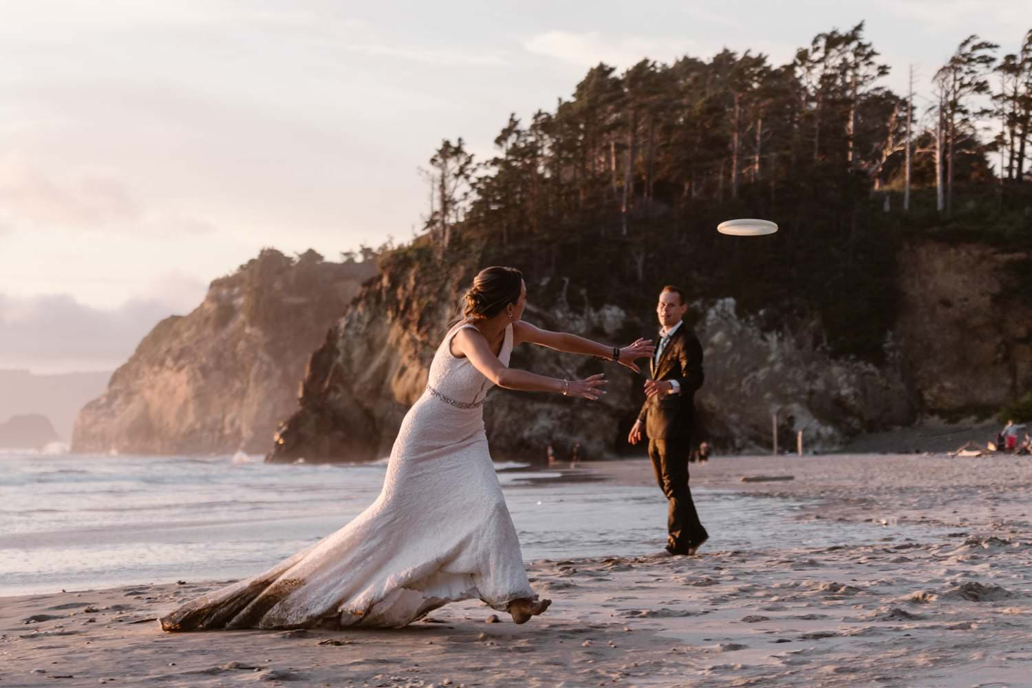 Bride and Groom playing frisbee at Hug Point Elopement