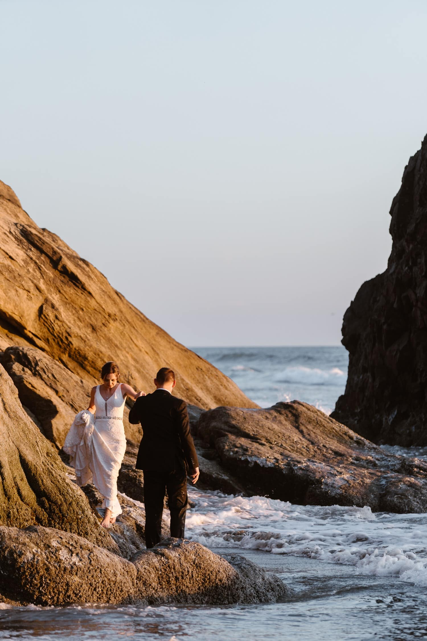 Bride and Groom hiking near ocean at Hug Point & Cannon Beach Elopement