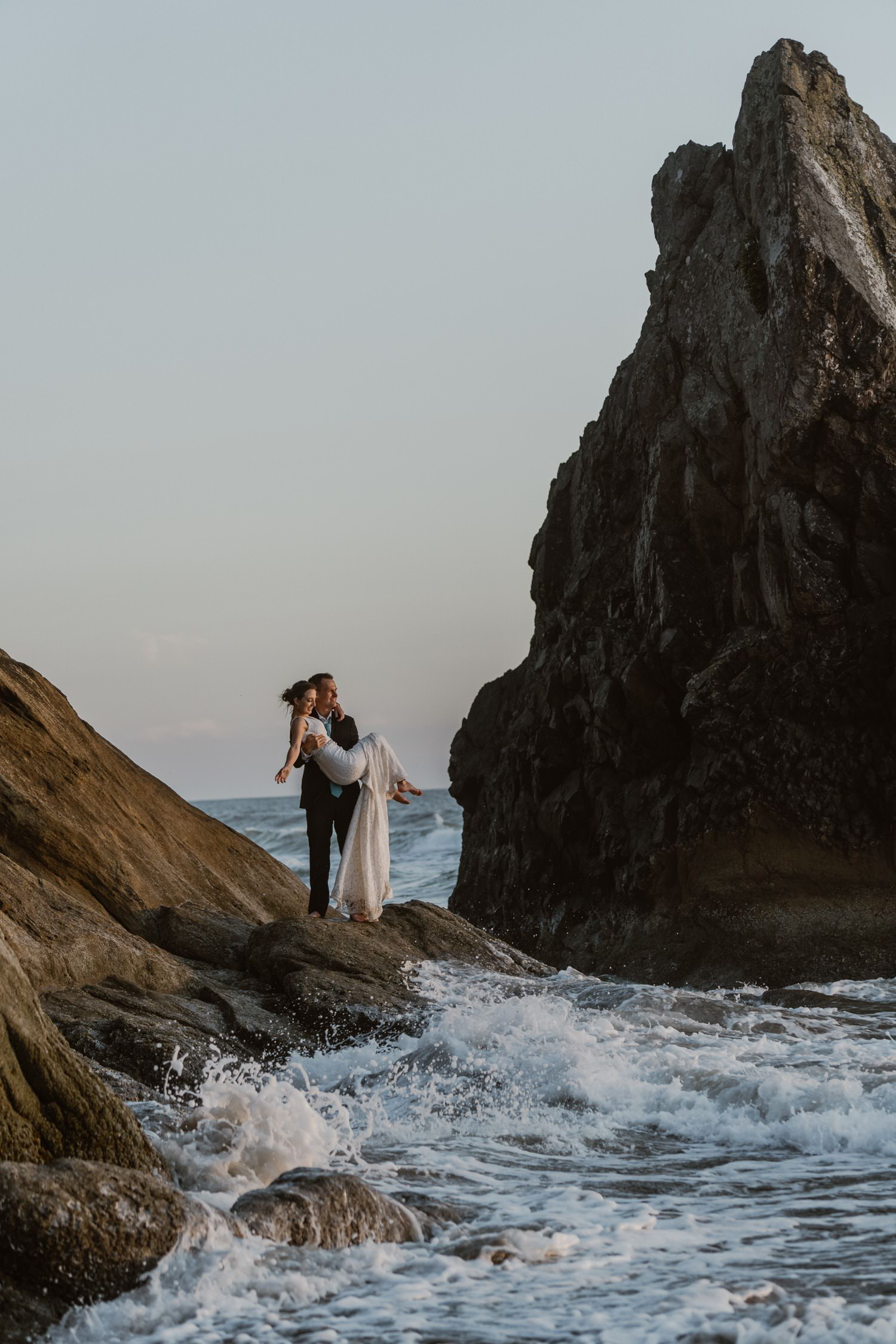 Groom holding bride on rock near ocean at Hug Point & Cannon Beach Elopement