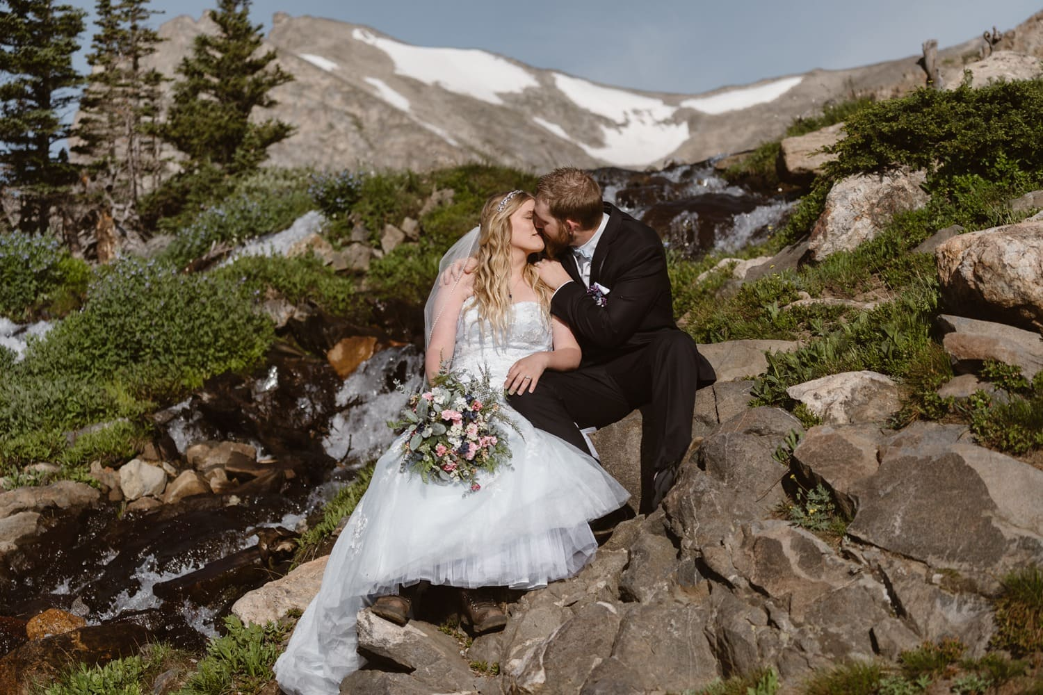 Bride and Groom Kissing Near Waterfall at Colorado Adventure Elopement