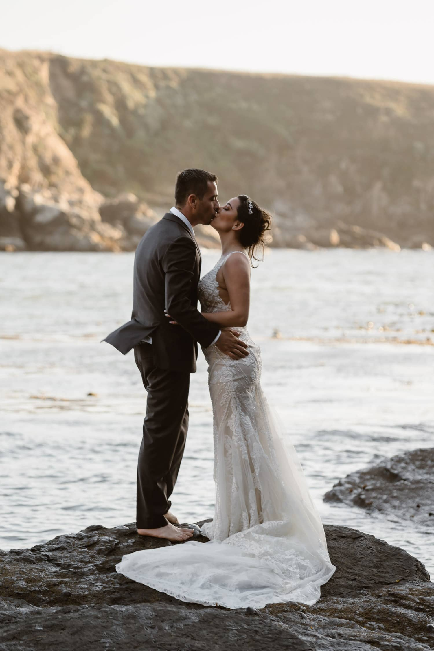 Bride and Groom kissing on rock in ocean at Big Sur Elopement