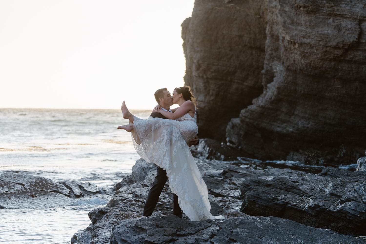 Groom holding bride on rock at the ocean at Big Sur Elopement