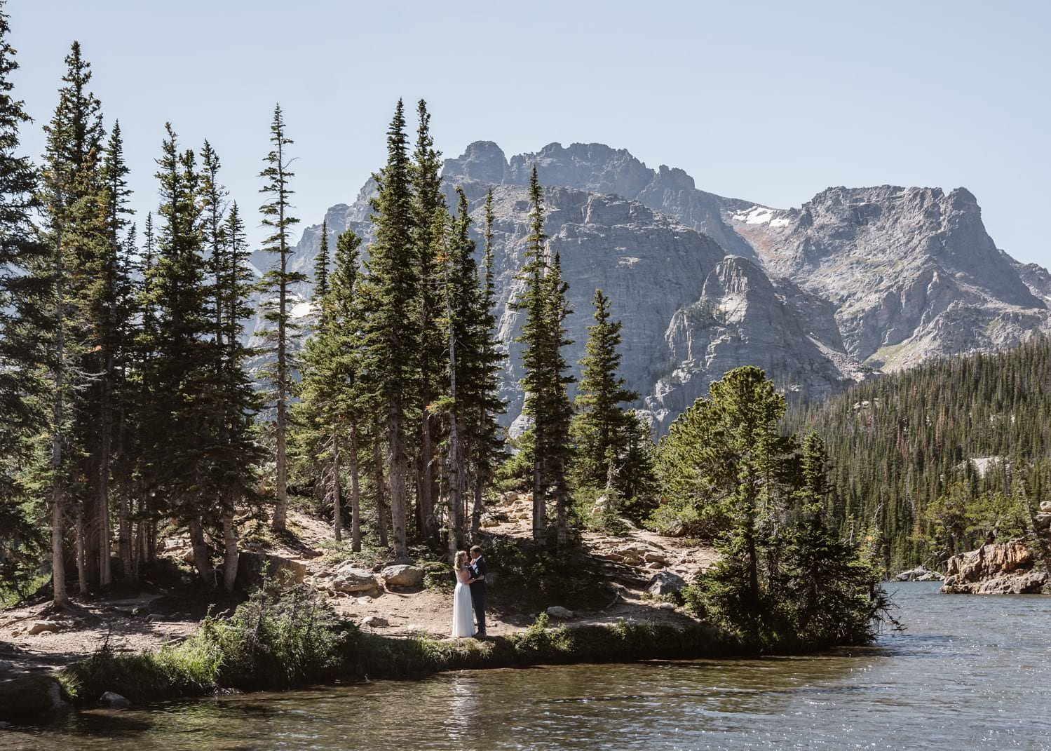 Bride and groom laughing at Loch Lake at Rocky Mountain National Park  Hiking Elopement