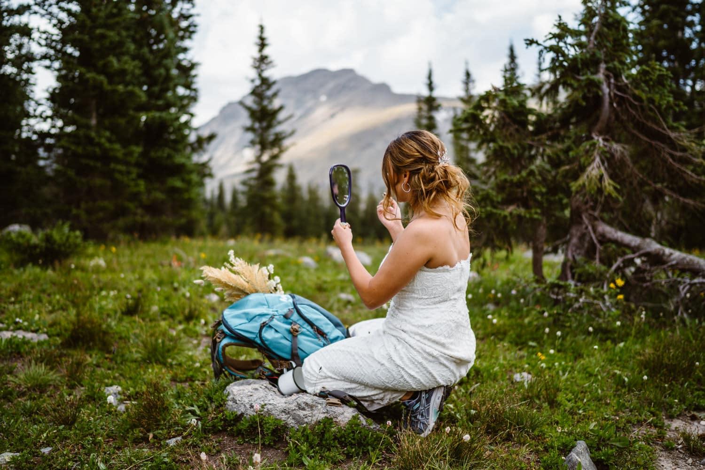 Bride Putting on Makeup Hiking Adventure Elopement
